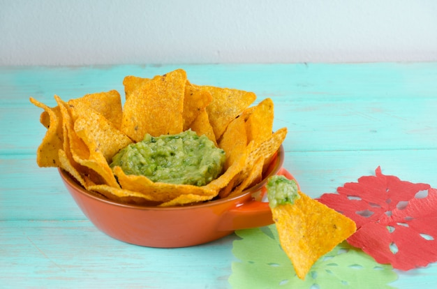 Nachos with guacamole on blue wooden table.