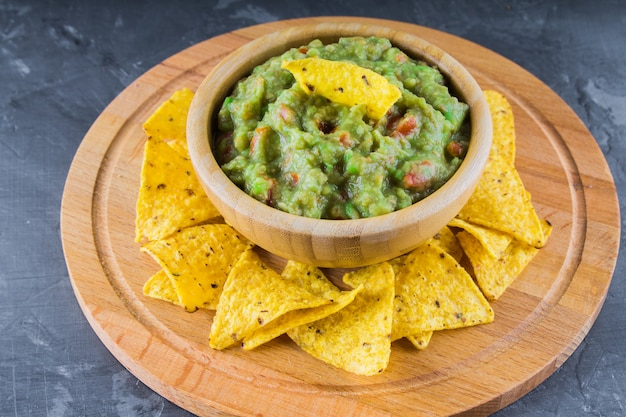 Nachos with guacamole on a gray background
