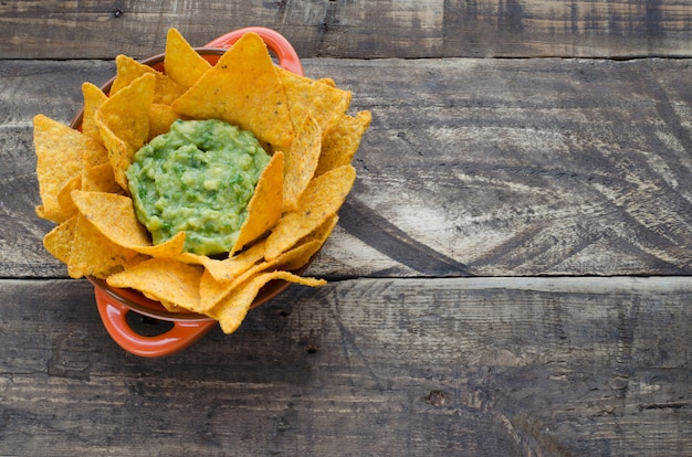 Nachos with guacamole on rustic wooden background.