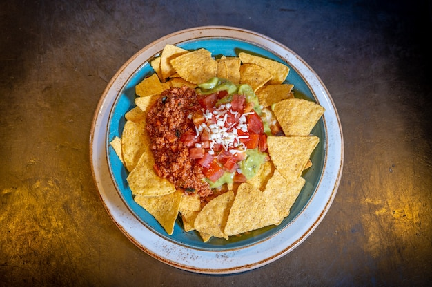 Nachos with guacamole and tomato sauce on a black background, on a blue plate