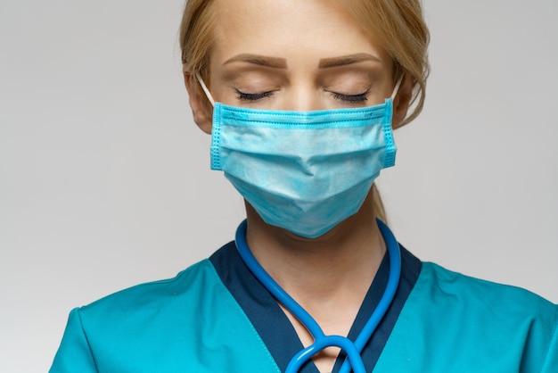 防護マスクとラテックス手袋を身に着けている医師看護師女性-祈ってnad希望のジェスチャー