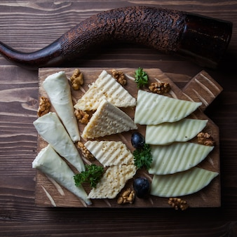 Nadugiとブドウとまな板でホーンを飲むトップビューチーズプレート