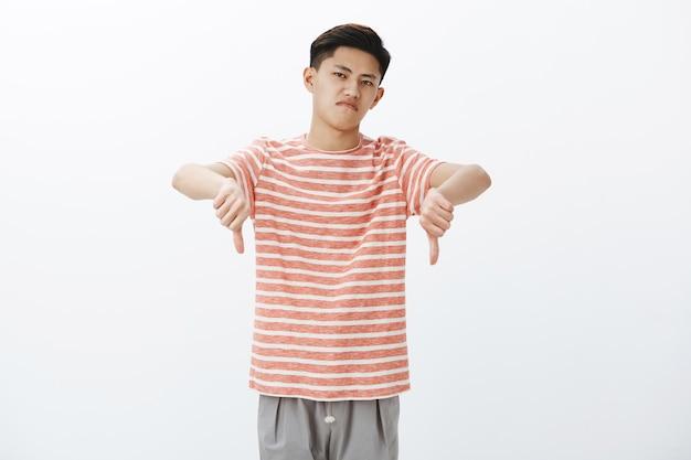 Нет отрицательный отзыв. раздосадованный и недовольный привлекательный молодой азиатский мужчина в полосатой футболке показывает большие пальцы вниз, подняв голову с презрением, но не впечатлен