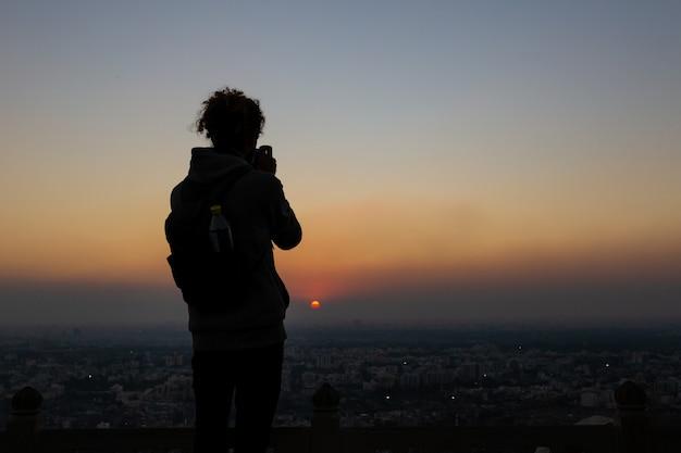 Nahagarhフォートジャイプールで夕日に対して写真を撮る男のシルエット。