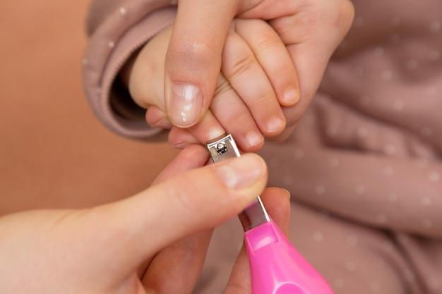 Маникюр для ногтей и пальцев для ребенка от руки мама держит маленькие ножницы, чтобы с любовью и заботой обрезать ноготь, чтобы он был чистым