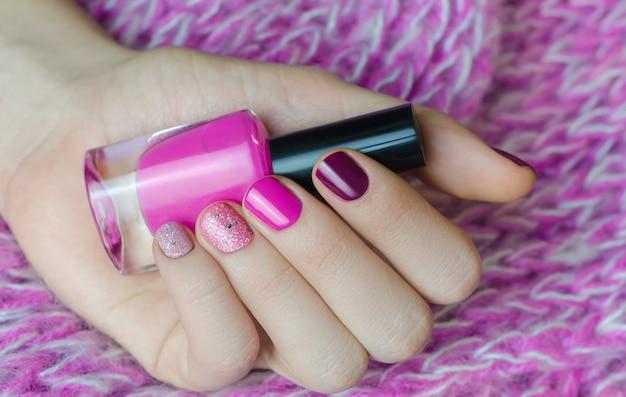 キラキラとネイルアート。ピンクのマニキュアで美しい女性の手