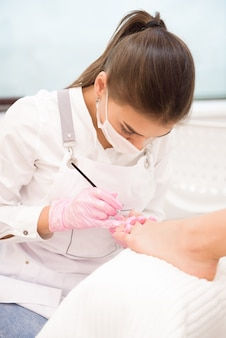 Nail artist in beauty salon making pedicure for clients feet.