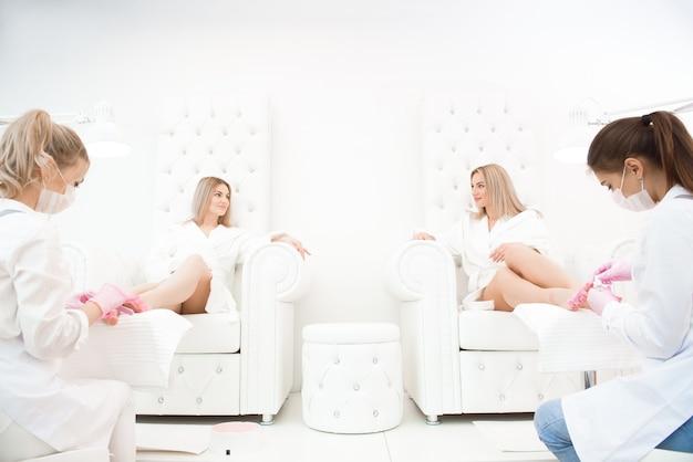 クライアントの足のためのペディキュアを作る美容院のネイリスト。