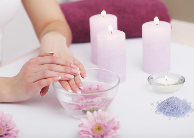ネイルケア。ビューティーサロンでの自然な爪と美しい女性の手のクローズアップ。屋内の水の入った透明なガラスのボウルに女性の爪を浸します。スパマニキュアのコンセプトです。高解像度