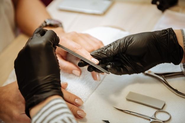爪やすり。マニキュアを作る爪やすりを使用しながら忙しいと感じているプロのマニキュアマスターのクローズアップ