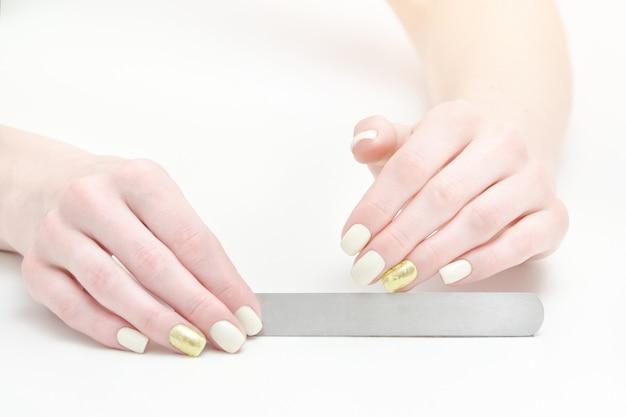 女性の手で爪やすり、テキストのための場所。ホワイトスペース