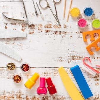 Пилочки, ножницы, плоскогубцы, блестки и лаки для ногтей на белом деревянном фоне.