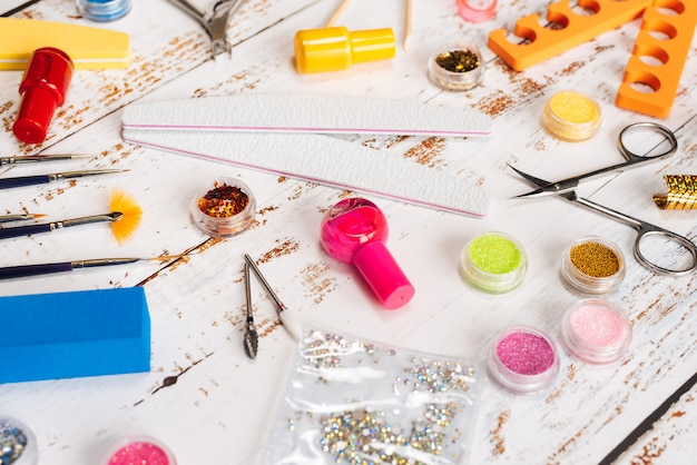 Nail files, scissors, pliers, sequins and nail polishes on a white wooden background.