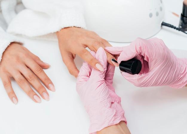 Igiene e cura delle unghie e persona che indossa i guanti