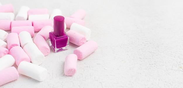 マニキュアとマシュマロ。白い背景の上のマシュマロ。マニキュアに関する記事。美容。装飾化粧品。