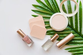 Nail polish bottle; lipstick; sponge and compact on green leaf against white background