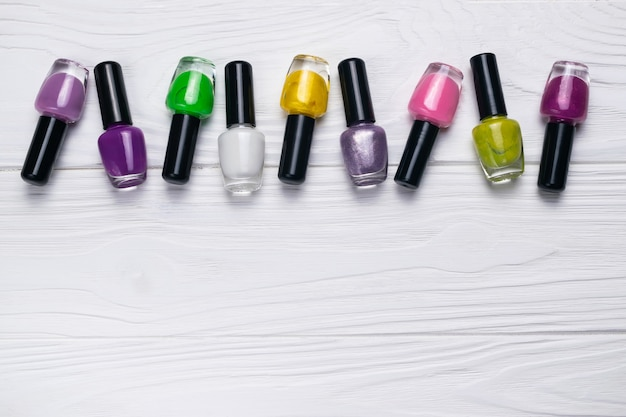 Nail polish bottles in different colors on white wooden background