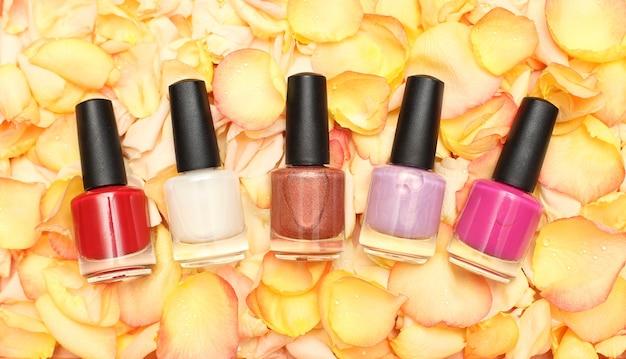 Nail polish bottles on rose petals