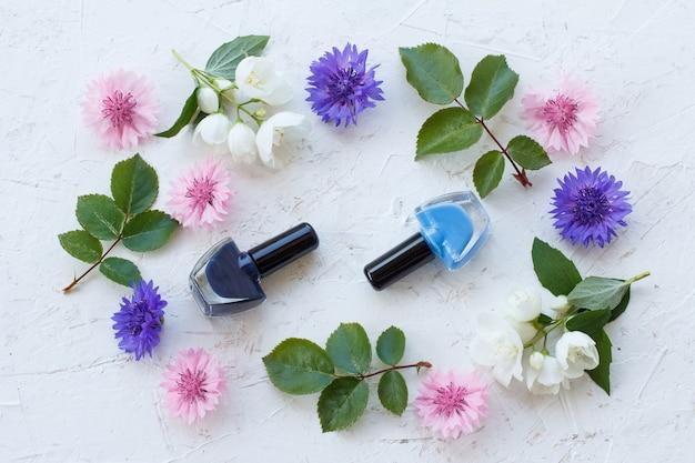 Бутылки лака для ногтей с васильками и цветами жасмина, зеленые листья на белом фоне. вид сверху.