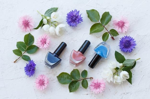Бутылки лака для ногтей с васильками и цветами жасмина, зеленые листья на белой поверхности