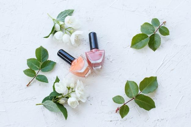 Бутылки лака для ногтей с цветами жасмина и зелеными листьями на белой поверхности