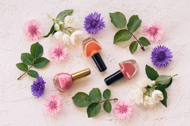 Бутылки лака для ногтей с цветами жасмина, васильками и зелеными листьями на белой поверхности