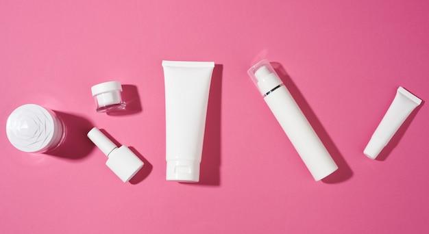 분홍색 배경에 화장품용 매니큐어, 항아리, 빈 흰색 플라스틱 튜브. 크림, 젤, 혈청, 광고 및 제품 판촉용 포장, 평면도