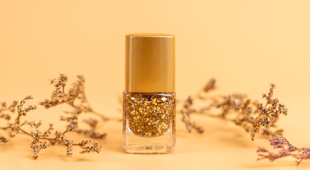 Лак для ногтей красивых золотых цветов на оранжевом фоне.