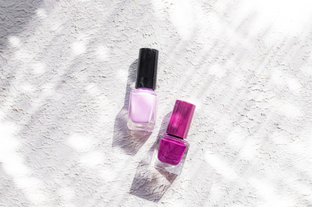 Лак для ногтей на белом фоне с тенями