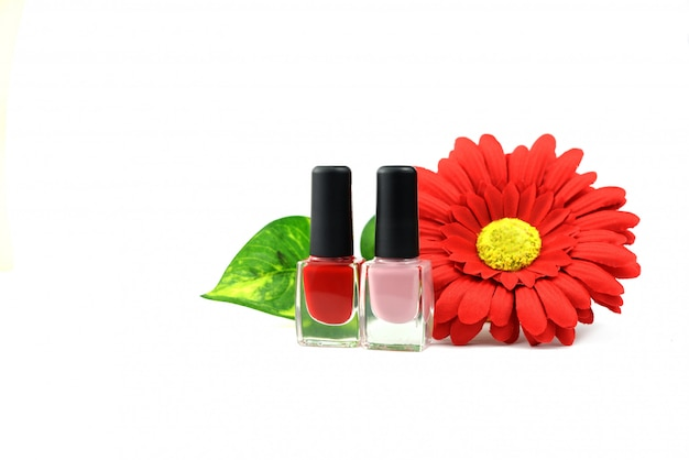 Nail polish red and pink cosmetics with flowers on a white  background