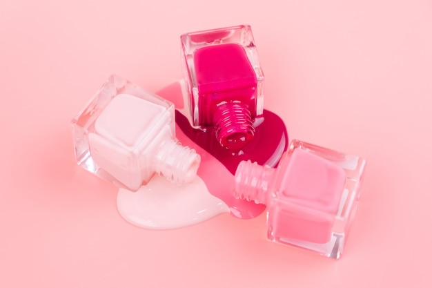 Nail polishes drip on a pink surface