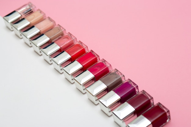 Лаки для ногтей на розовом и белом фоне концепции