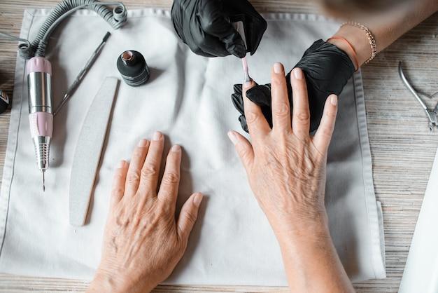 Маникюрный салон. мастер маникюра красит женские ногти лаком, крупный план. уход за ногтями, вид сверху.