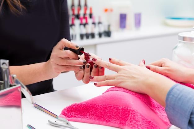 Маникюрный салон женщина рисует цвет лака для ногтей в руках