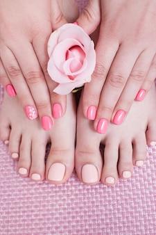 Спа-процедура для ногтей. маникюр и педикюр. женские руки и ноги на розовом фоне вид сверху. результат процедуры спа салона