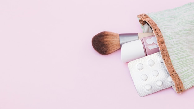 Nail varnish bottle; makeup brush and pills blister pack out from pouch against pink background