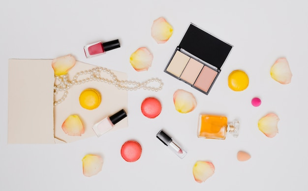 Nail varnish bottle; rose petals; necklace; lipstick; macaroons and perfume bottle isolated on white background