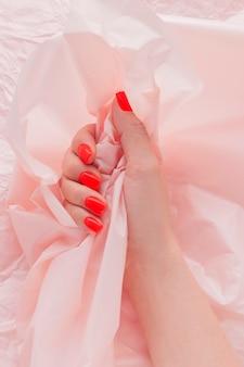 Дизайн ногтей. рука с ярко-красным маникюром. рука сжимает мятую розовую бумагу.