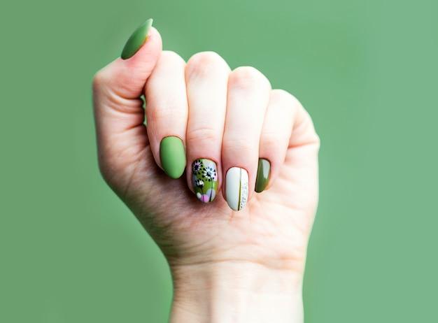 ネイルデザイン。緑に明るい緑と白のマニキュアを持つ手