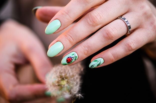 ネイルデザイン。花と明るいグリーンのマニキュアの手。女性の手のクローズアップ。アートネイル。