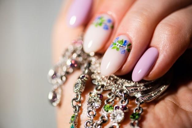 ネイルデザイン。明るいライラックと春の花と白いマニキュアの手。女性の手のクローズアップ。アートネイル。