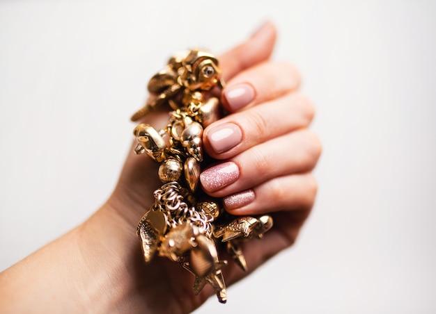 ネイルデザイン。白い背景の上の明るいヌードマニキュアと手。女性の手のクローズアップ。アートネイル。