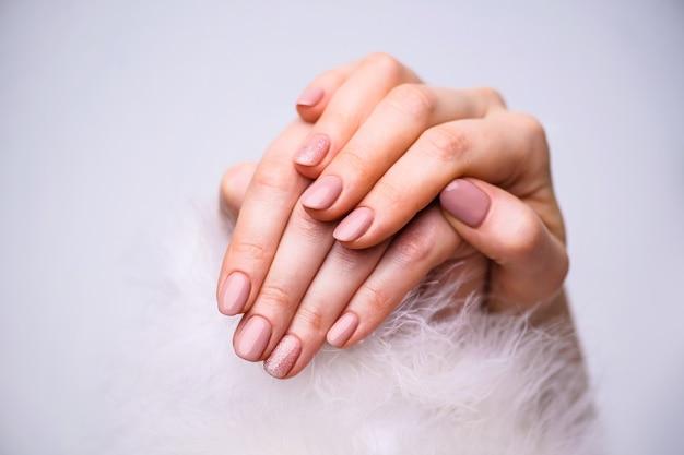 ネイルデザイン。灰色の明るいピンクの春のマニキュアと手