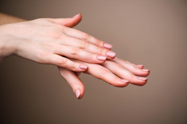 ネイルデザイン。明るいピンクの春のマニキュアと手