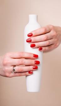 ネイルデザイン。背景に真っ赤な春のマニキュアと手。女性の手のクローズアップ。アートネイル。