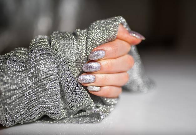 ネイルデザイン。明るいシルバーのクリスマスマニキュアの手。女性の手のクローズアップ。アートネイル。