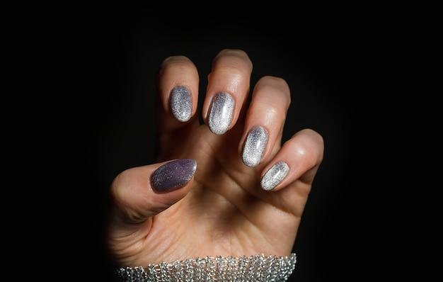 ネイルデザイン。黒の背景に明るいシルバーのクリスマスマニキュアと手。女性の手のクローズアップ。アートネイル。