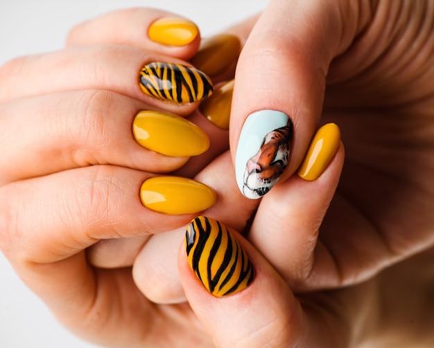 ネイルデザイン。背景に明るい黄色のマニキュアの手。女性の手のクローズアップ。アートネイル。タイガーマニキュア