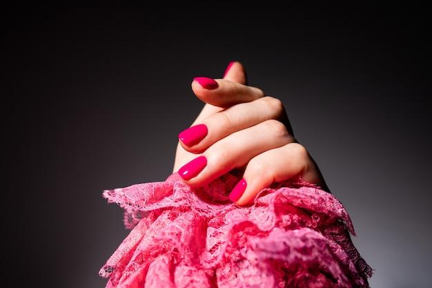 ネイルデザイン。灰色のスペースにピンクの夏のマニキュアと手。女性の手のクローズアップ。アートネイル。