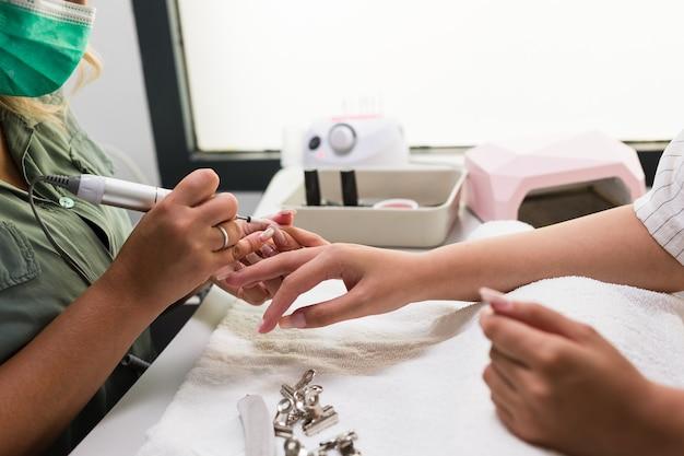 살롱 젊은 라틴 여자 손 케어 유리 섬유 치료에서 손톱 매니큐어 라이프 스타일 매니큐어